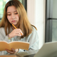 Teenage woman holding pencil and notebook serious gesture with laptop on desk,online learning. - PhotoDune Item for Sale
