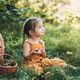 Girl in overalls sitting on the grass next to basket of vegetables - PhotoDune Item for Sale