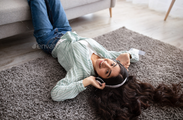 Above view of lovely Indian lady in headphones listening to music, lying on soft carpet at home - Stock Photo - Images