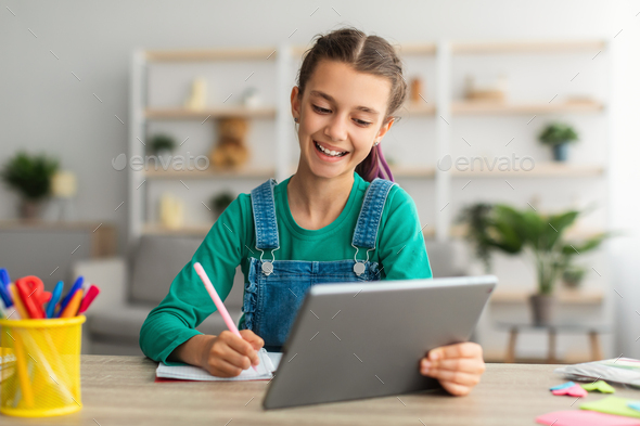 Girl sitting at table, using tablet, writing in notebook - Stock Photo - Images