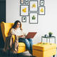 woman with long loose curly hair sits in armchair and types on laptop - PhotoDune Item for Sale
