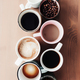 Multiple coffee cups, milk, beans and ground coffee in jar on wooden background - PhotoDune Item for Sale