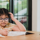 A Child girl in glasses is drawing in a notebook with a tablet on the table. - PhotoDune Item for Sale