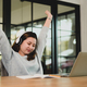 A woman stretches her arms above her head to relieve fatigue while working on her laptop. - PhotoDune Item for Sale