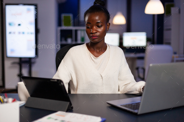 Workaholic tired multitasking african american entrepreneur analyzing financial graphs - Stock Photo - Images