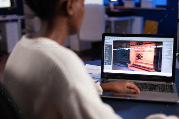 African american game developer testing new game working late at night - Stock Photo - Images