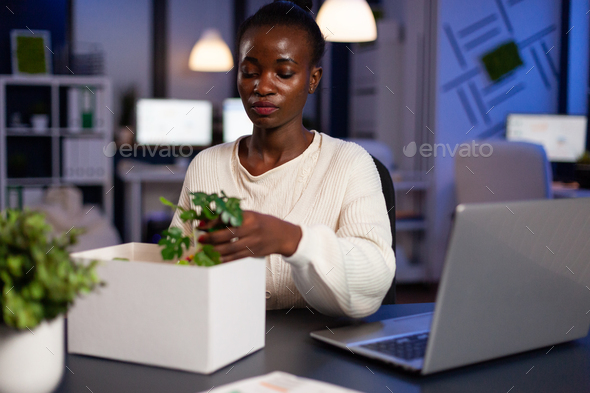 Portrait of resigned dismissed african american businesswoman packing objects - Stock Photo - Images