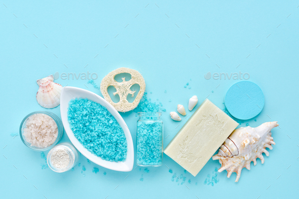 Sea salt, cream, soap, sponges and shells in cosmetics set for spa on blue background - Stock Photo - Images