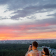 Young couple standing on rooftop patio while photographing sky at sunset - PhotoDune Item for Sale