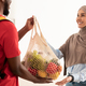 Black deliveryman giving net mesh bag with groceries to woman - PhotoDune Item for Sale