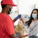 Black deliveryman in mask giving net mesh bag to woman - PhotoDune Item for Sale