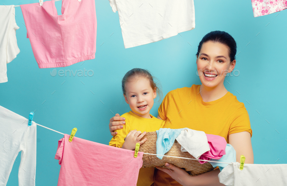 woman and girl hanging clothes on a rope - Stock Photo - Images