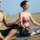 Caucasian couple meditate at the beach - PhotoDune Item for Sale