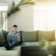 Young guy sitting at green sofa with gray laptop and black phone - PhotoDune Item for Sale