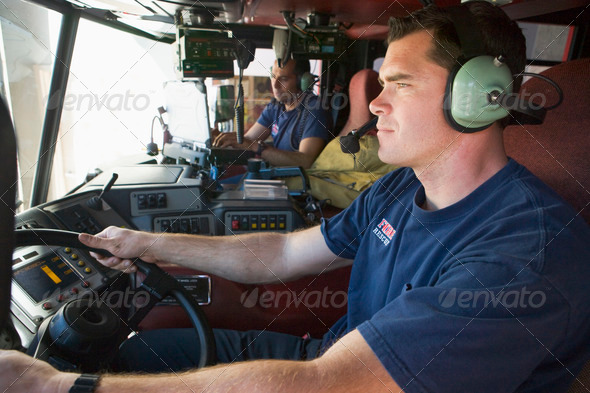 A firefighter driving a fire engine - Stock Photo - Images