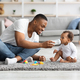 Caring young black dad giving water to his little baby at home - PhotoDune Item for Sale