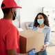 Black deliveryman in disposable mask giving box to woman - PhotoDune Item for Sale
