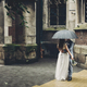 Stylish bride and groom kissing under umbrella on background of old church in rain. Provence wedding - PhotoDune Item for Sale