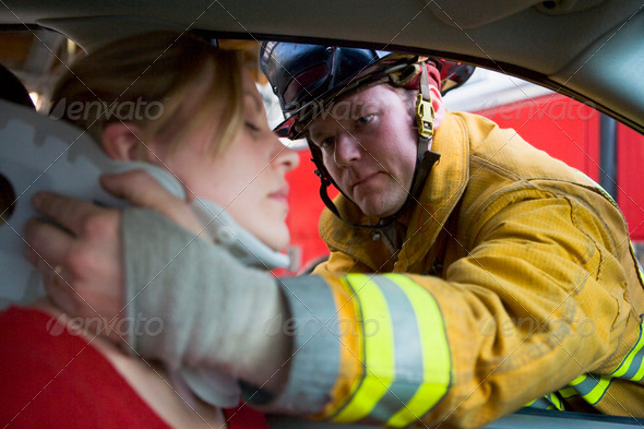 Firefighters helping an injured woman in a car - Stock Photo - Images