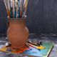 Paint brush in clay jug and palette on table background. Paintbrush for painting as art still life - PhotoDune Item for Sale