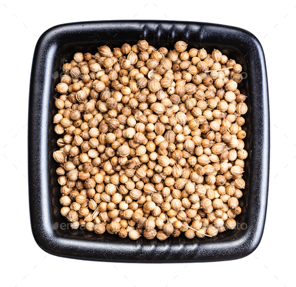 dried coriander seeds in black bowl isolated - Stock Photo - Images