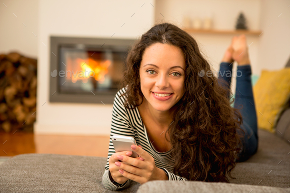 Woman with her cellphone at home - Stock Photo - Images