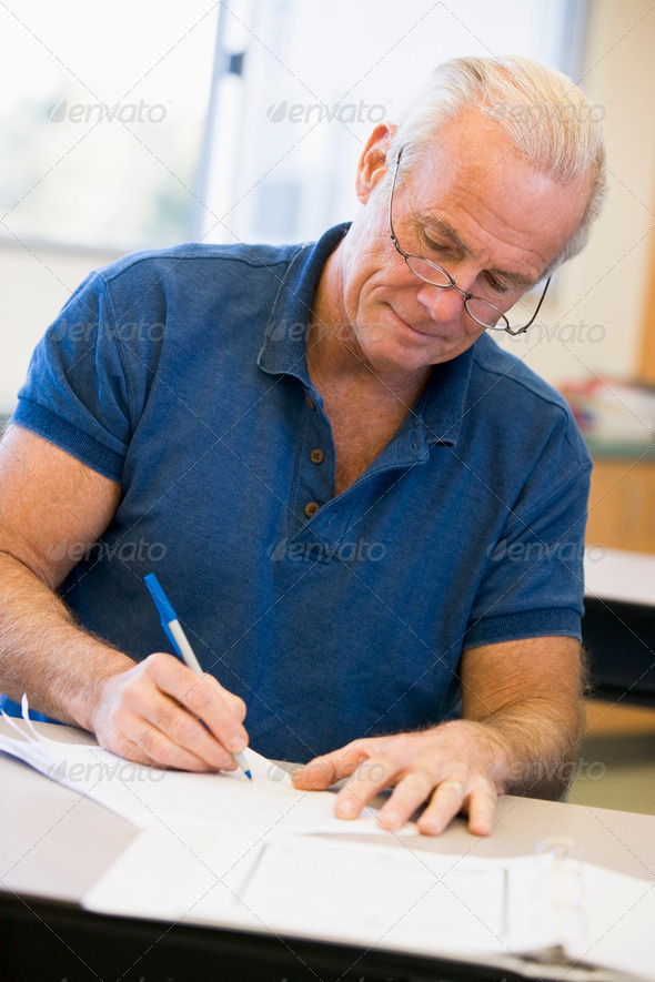 Mature male student writing in class - Stock Photo - Images