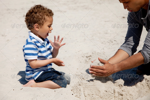 Kid Looking as His Dad Makes Sand Castle - Stock Photo - Images