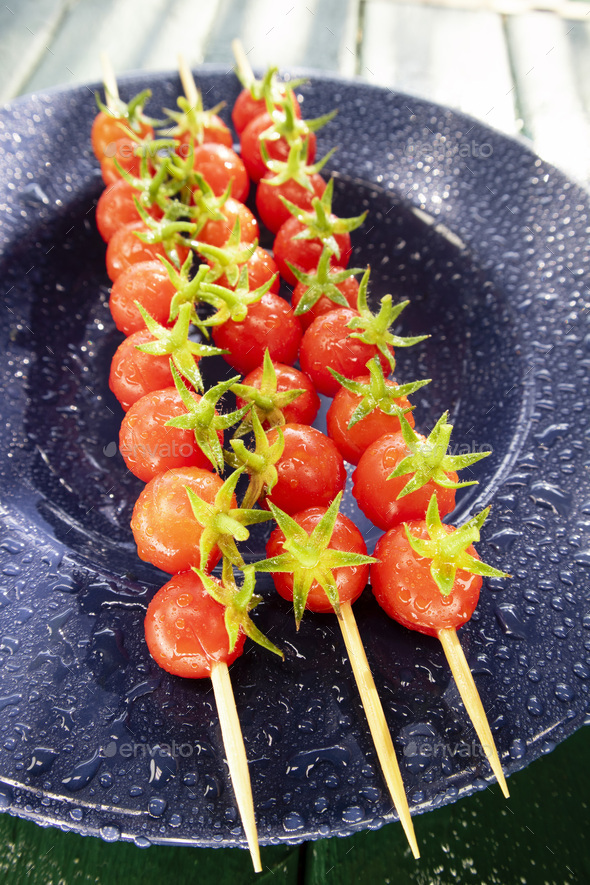 Skewer of red Pachino tomatoes over blue plate - Stock Photo - Images