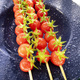 Skewer of red Pachino tomatoes over blue plate - PhotoDune Item for Sale