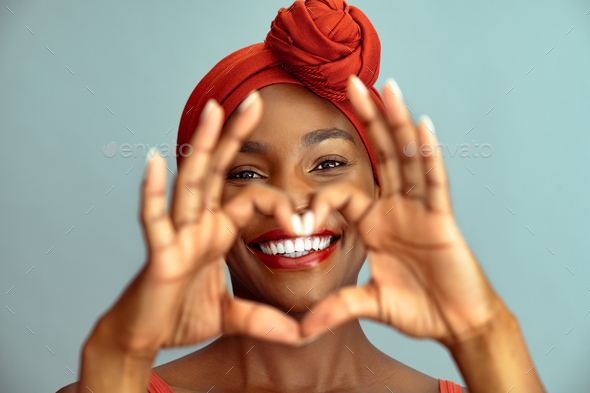 Black mature woman making heart shape and smile - Stock Photo - Images
