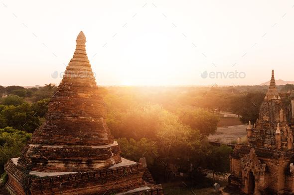 Buddhist temple shape against sun light during sunrise - Stock Photo - Images