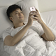 Man using smartphone in bed - PhotoDune Item for Sale