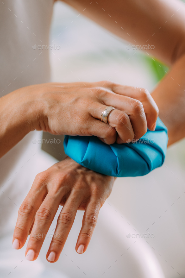 Wrist Pain Treatment. Woman Holding Ice Bag Compress on a Painful Wrist. - Stock Photo - Images