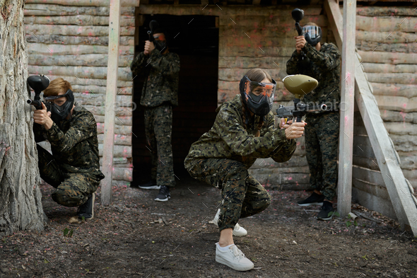 Paintball team fights on playground in the forest - Stock Photo - Images