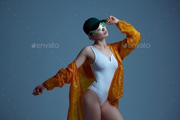 Futuristic woman in raincoat, cap and glasses - Stock Photo - Images