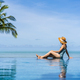 Young woman traveler relaxing and enjoying by a tropical resort pool while traveling for summer - PhotoDune Item for Sale