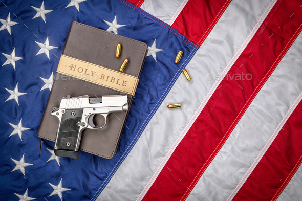 Gun on Holy Bible with American Flag - Stock Photo - Images
