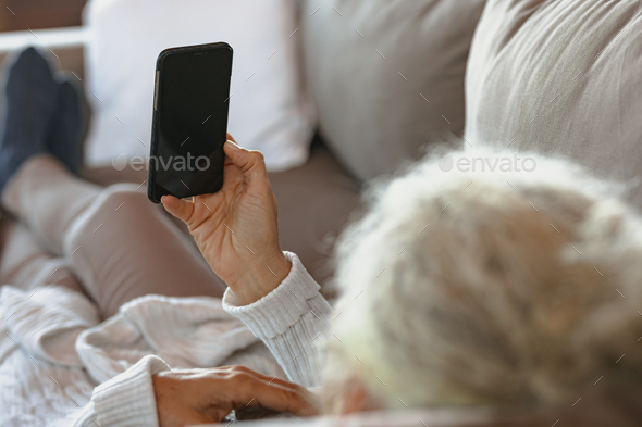 Senior caucasian woman laying and using smartphone in the modern living room - Stock Photo - Images