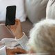 Senior caucasian woman laying and using smartphone in the modern living room - PhotoDune Item for Sale