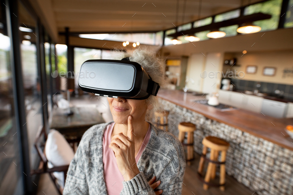 Happy senior caucasian woman using vr headset in the modern living room - Stock Photo - Images