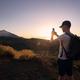 Man photograps by mobile phone against landscape - PhotoDune Item for Sale