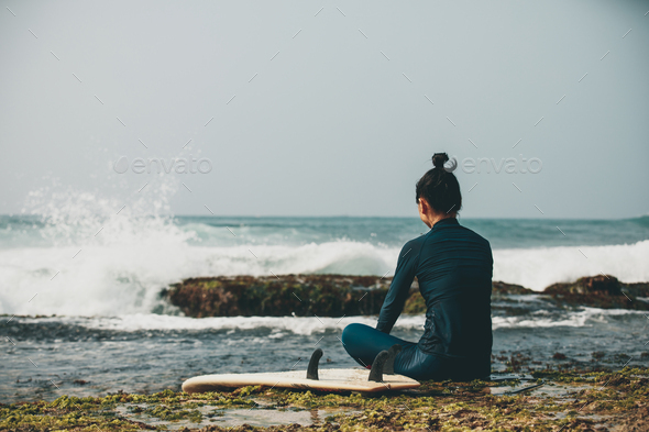 Woman surfer sit on reef looking at the waves - Stock Photo - Images