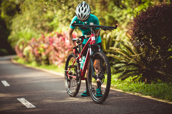 Woman cyclist adjust the seat height cycling on summer park trail - Stock Photo - Images