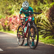 Woman cyclist adjust the seat height cycling on summer park trail - PhotoDune Item for Sale