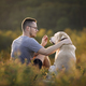 Man with dog sitting together on meadow - PhotoDune Item for Sale