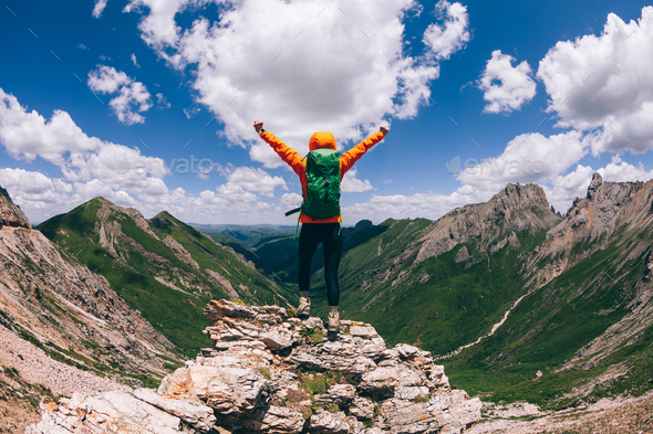 Successful woman backpacker hiking on alpine mountain peak - Stock Photo - Images