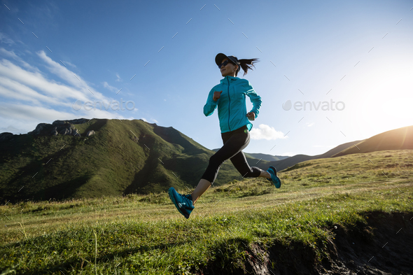 Young woman runner running at mountain top - Stock Photo - Images