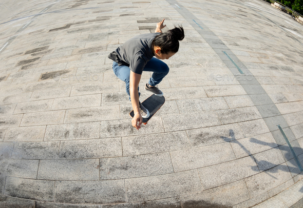 Asian woman skateboarder skateboarding in modern city - Stock Photo - Images