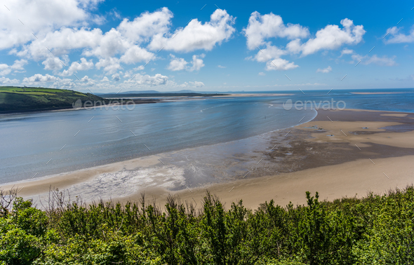 Panoramic shot of LLansteffan beach with clear blue water in southern Wales - Stock Photo - Images
